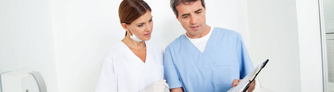 Two doctors consult with a view of a clipboard
